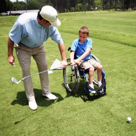 chlld in wheelchair golfing with instruction