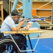 man in wheelchair using a table stand to shoot air rifle