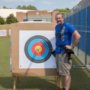 athlete standing next to target posing next to his arrows