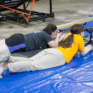 air rifle athlete laying prone shooting next to spotter