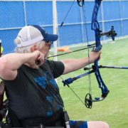 man in wheelchair shooting archery