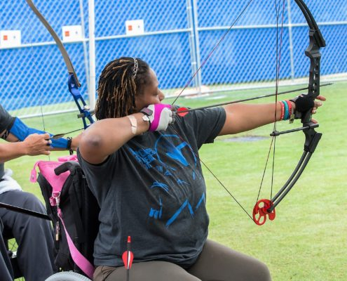 woman in wheelchair shooting archery