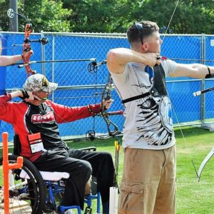 Man standing shooting archery next to man seated in wheelchair shooting archery