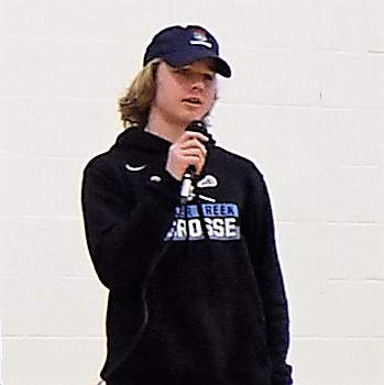 young man wearing baseball cap holding microphone