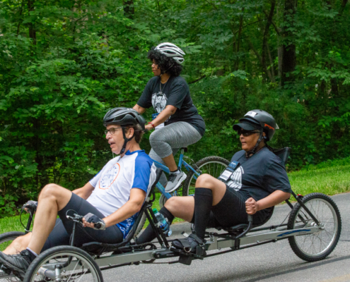 Athletes pedaling a tandem recumbent cycle with an athlete pedaling an upright cycle