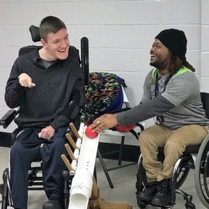 Coach in wheelchair assisting athlete in powerwheelchair use ramp to play boccia. Both are smiling and laughing