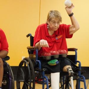 woman in wheelchair preparing to throw bocca ball