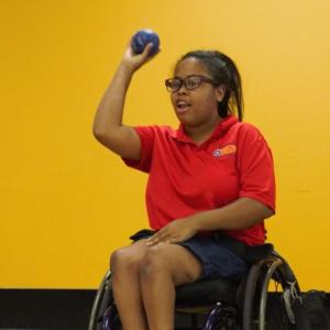 woman in wheelchair preparing to throw a boccia ball