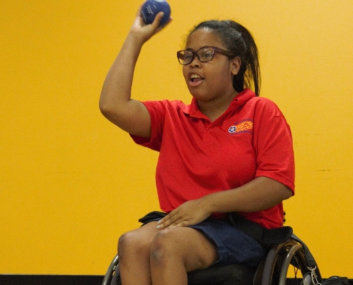 woman in wheelchair preparing to throw a boccia ball