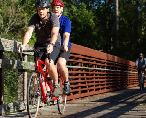 Pilot cyclist and cyclist with visual impairment pedaling a tandem cycle