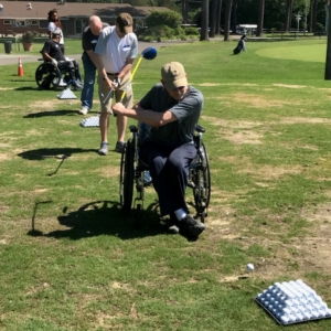 Several people with disabilities hitting golf balls including two athletes with wheelchairs