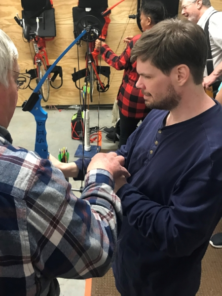 Man with visual impairment holding archery bow listening to instruction from coach