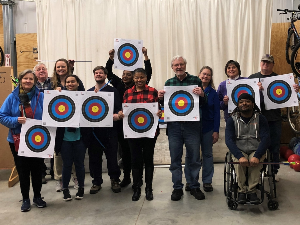 Group of athletes with visual impairments holding up archery targets with Bridge 2 Sports staff and coaches