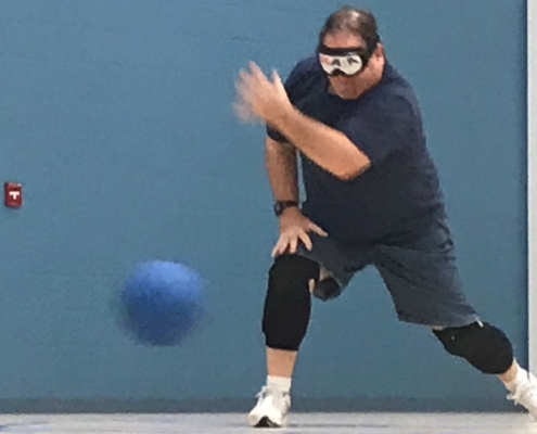 Goalball athlete standing and throwing the ball