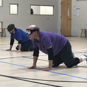 two goalball athletes on the floor preparing to defend