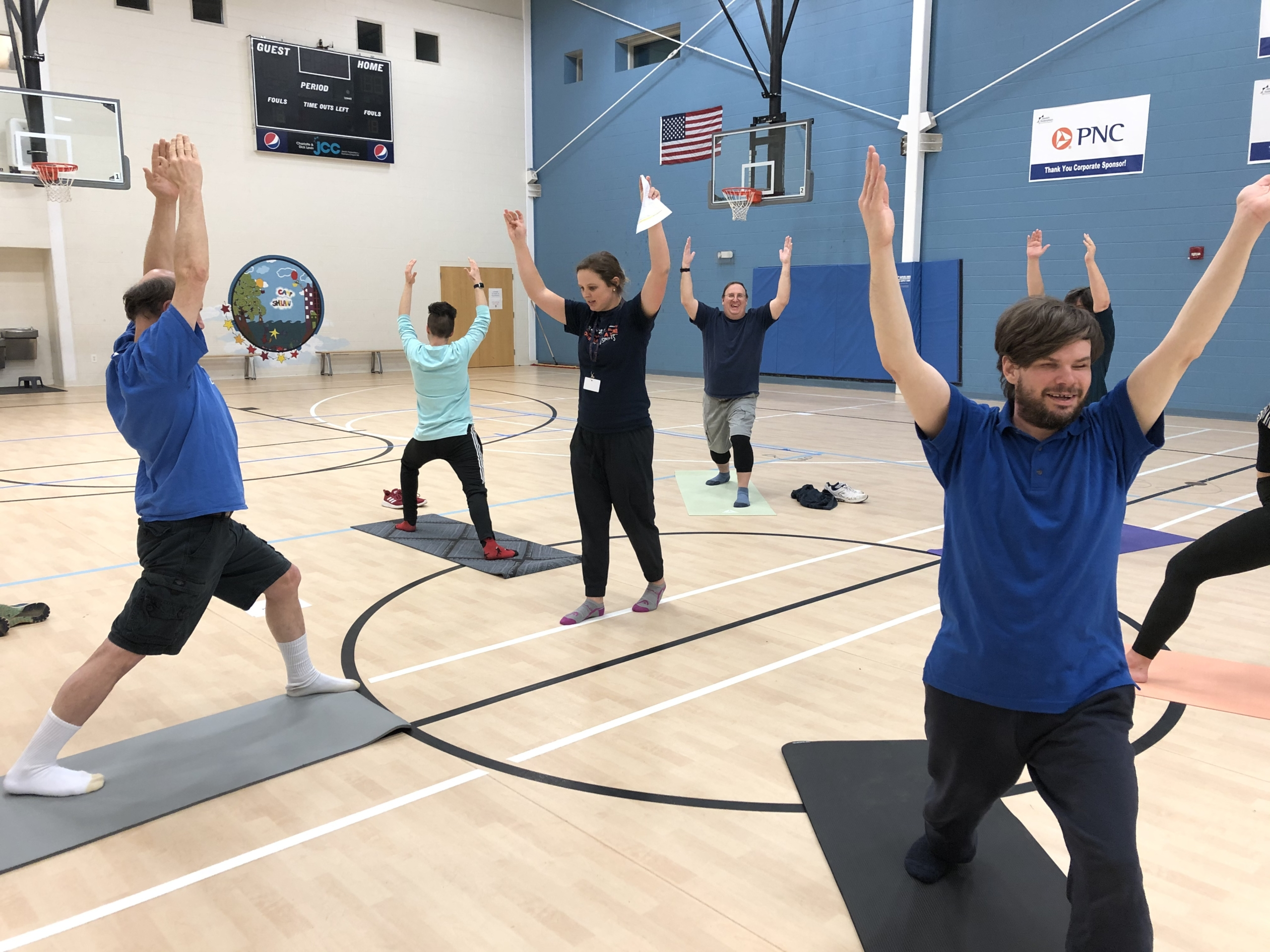 Athletes with visual impairments at Goalball practice doing yoga poses with arms over their heads with program intern Jessica in the middle leading the activity