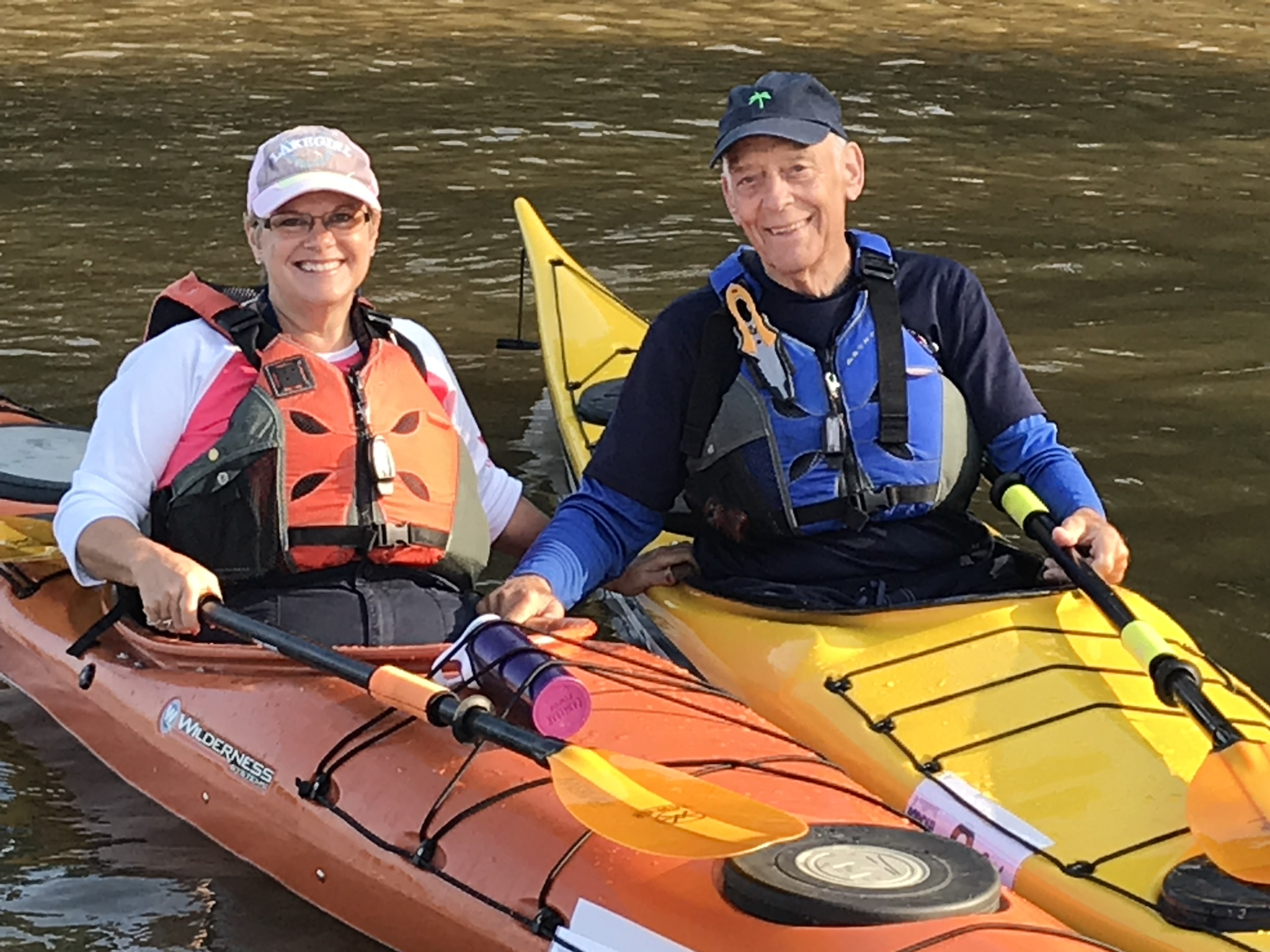 Whit Johnson and Gloria Johnson sitting in kayaks holding their boats next to each other