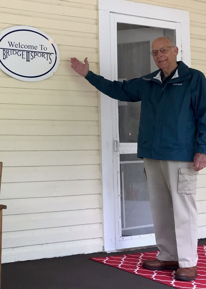 Whit Johnson standing next to Bridge 2 Sports office sign