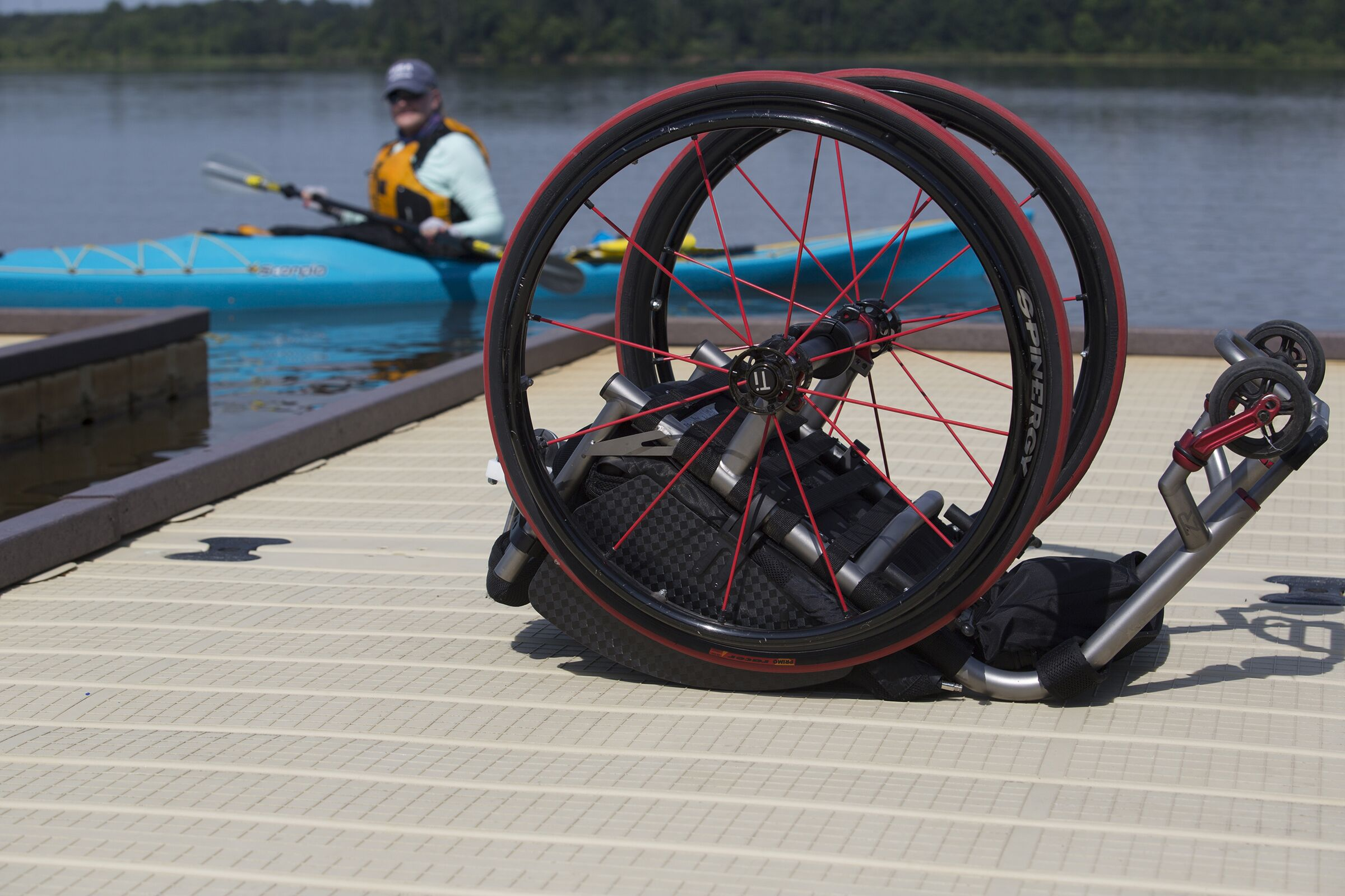 picture of Ashley in Kayak in background with an empty wheelchair in the foreground