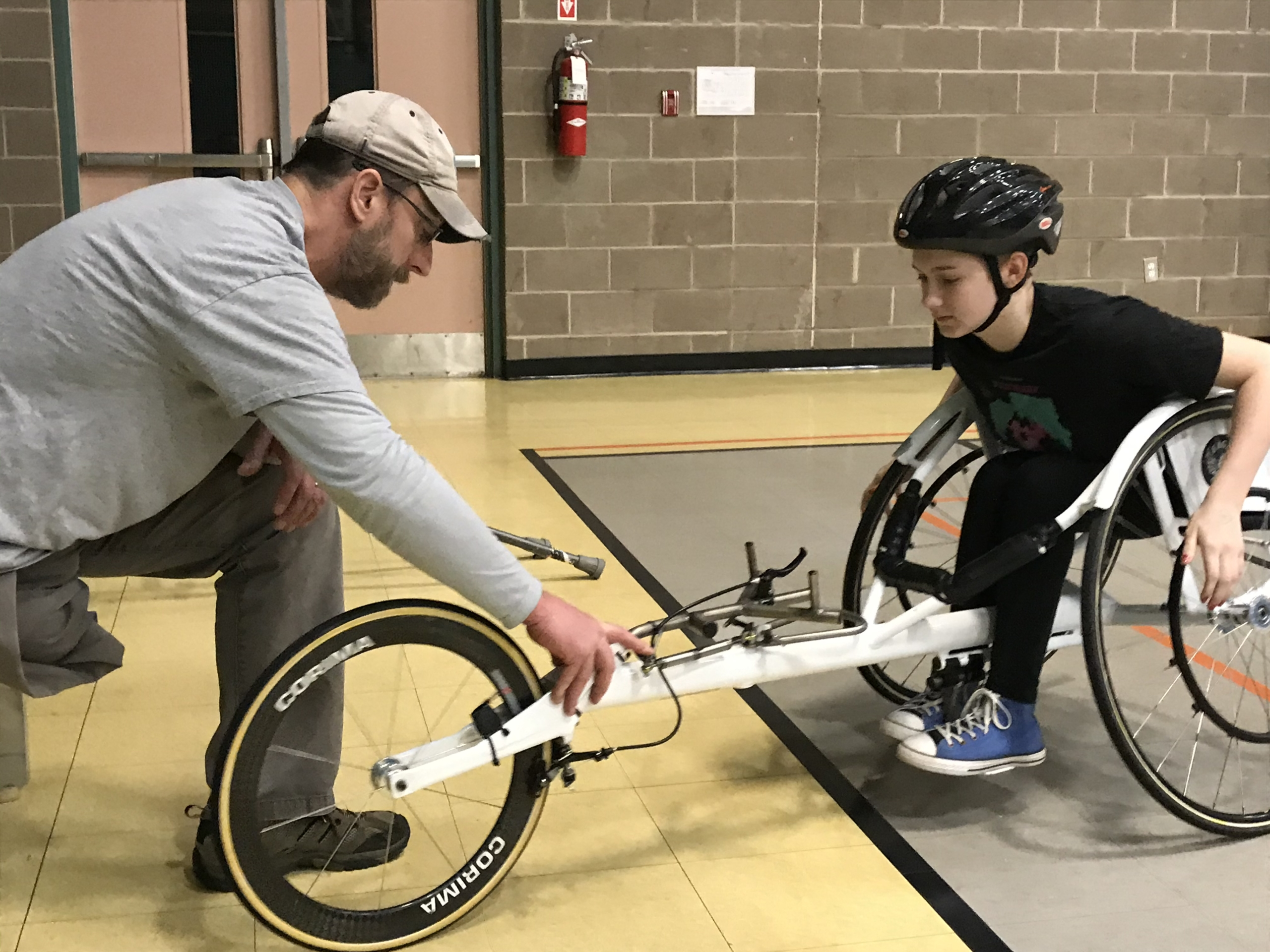 Wes Hall assisting young athlete find balance in wheelchair racing chair. Athlete is sitting opposite Wes with hands on rim.