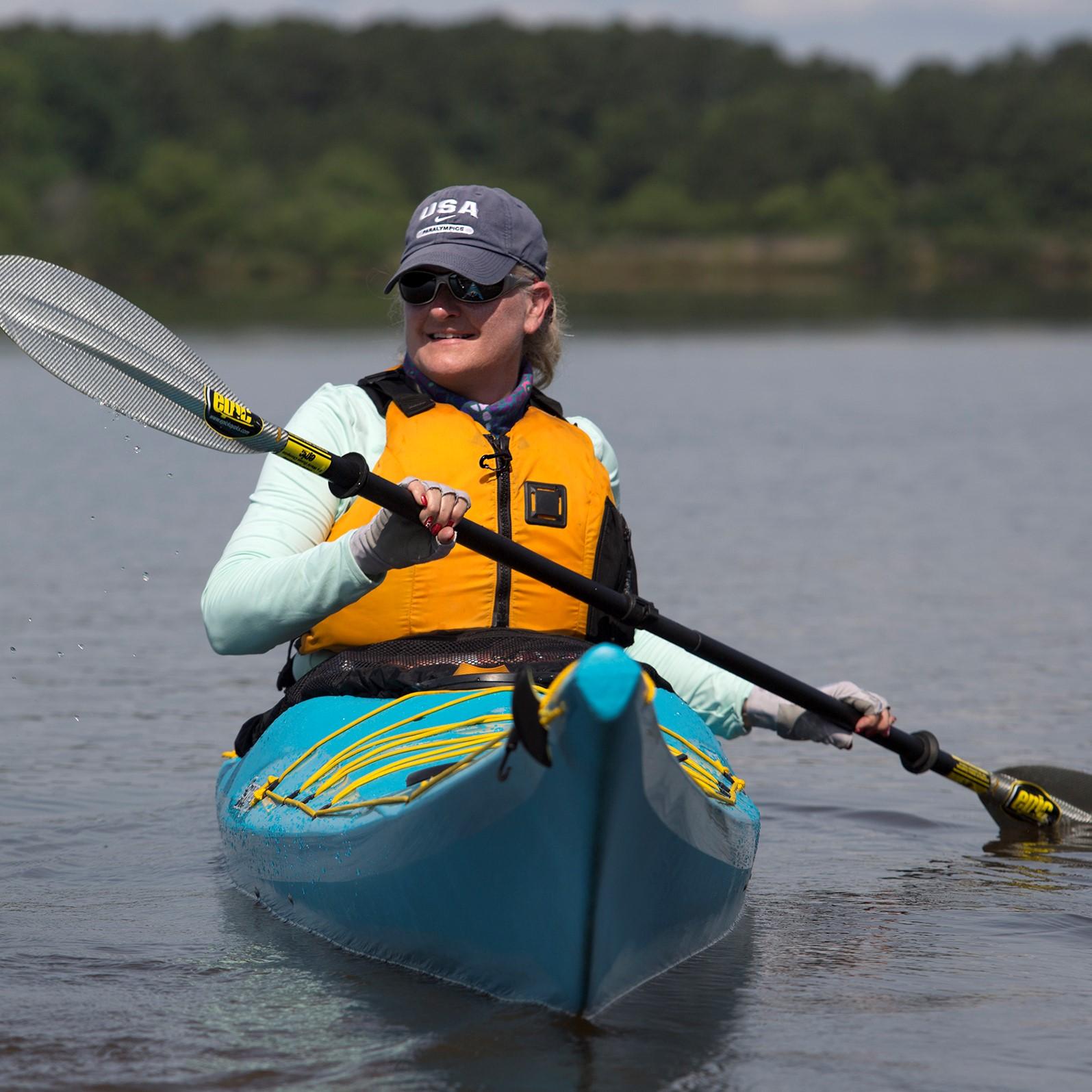 ashley thomas paddling in a blue kayak on lake crabtree