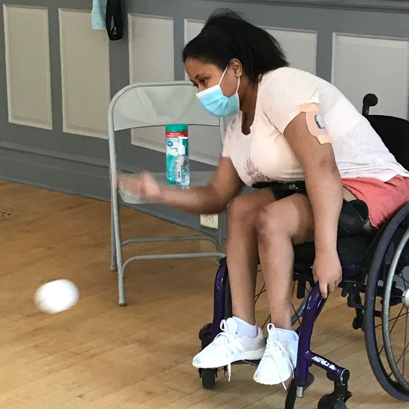 Female athlete using a wheelchair and throwing a boccia ball. She is wearing a mask.