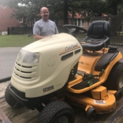 large riding lawn mower with man, Jeff Braddy from Latta Brothers, standing behind it.