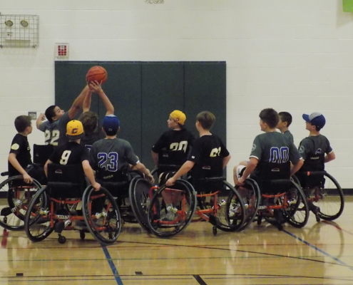 10 boys playing wheelchair basketball at Endless Sports event. Two are reaching for a ball in the air while the rest of the players watch