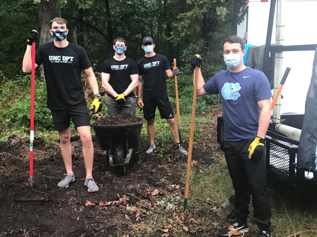 4 male college students standing in mulch holding shovels, rakes and a wheelbarrow. All are wearing masks.