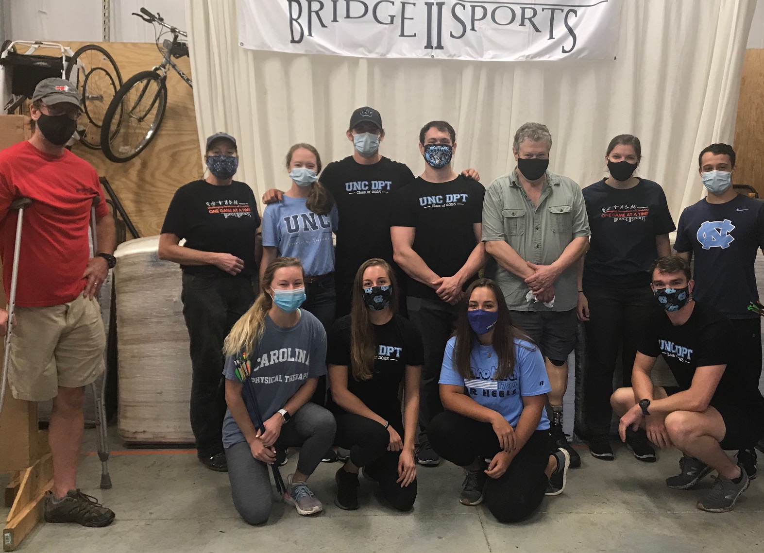 Group picture of 8 UNC Physical Therapy student volunteers posing with 4 Bridge 2 Sports staff members in the Bridge 2 Sports warehouse. All are wearing masks.