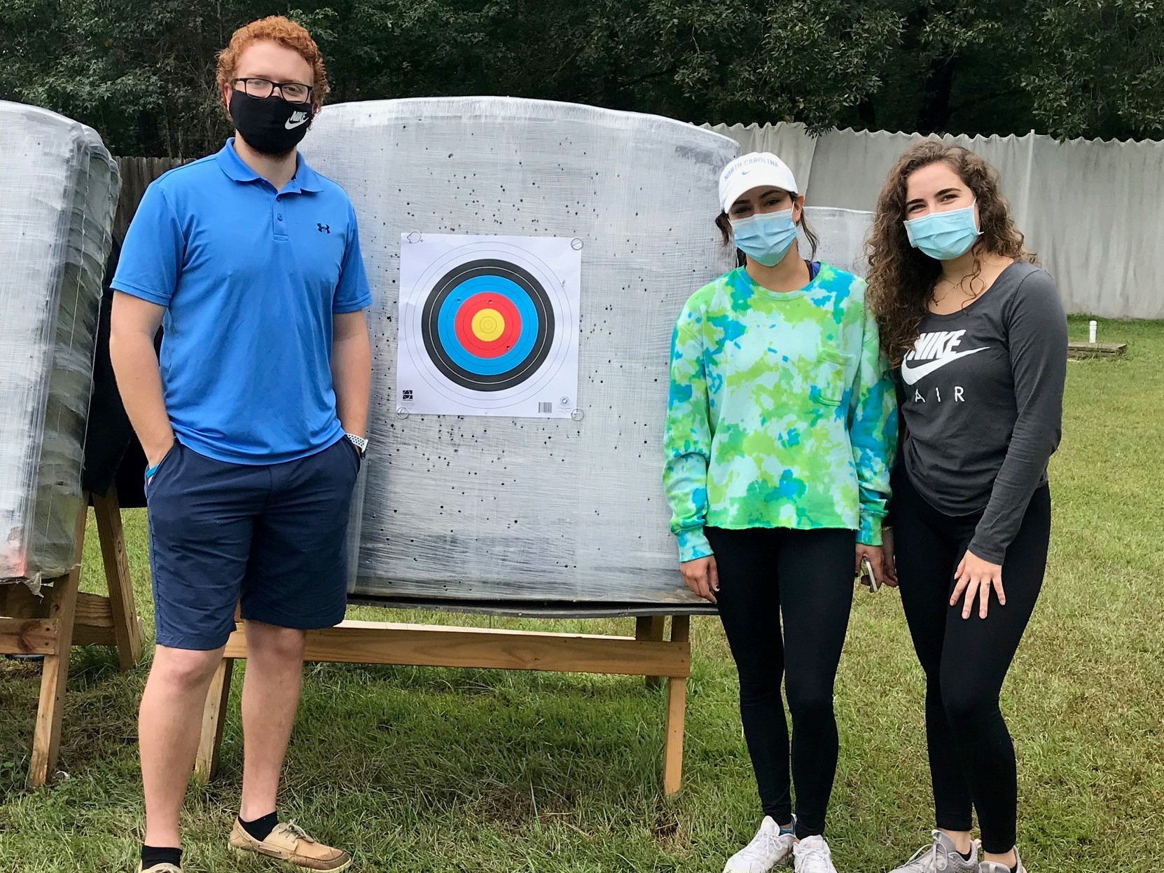3 college students- one male on the left with two females on the right posing next to an archery bale and target. All are wearing masks.