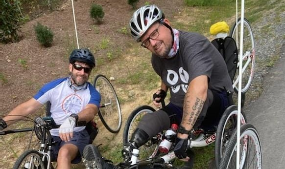 Two men in cycles posing for picture. Man on left is sitting in a handcycle and the man on the right has two prosthetic legs and is sitting in a recumbent bike.