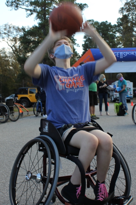 teen girl sits in sport wheelchair and shoots basketball at basket