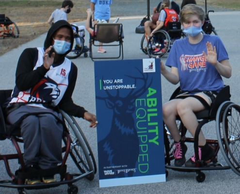 teen boy and teen girl sitting in sport wheelchairs waving wearing masks. a sign between them reads 'You are Unstoppable' Ablilty Equipped The Hartford