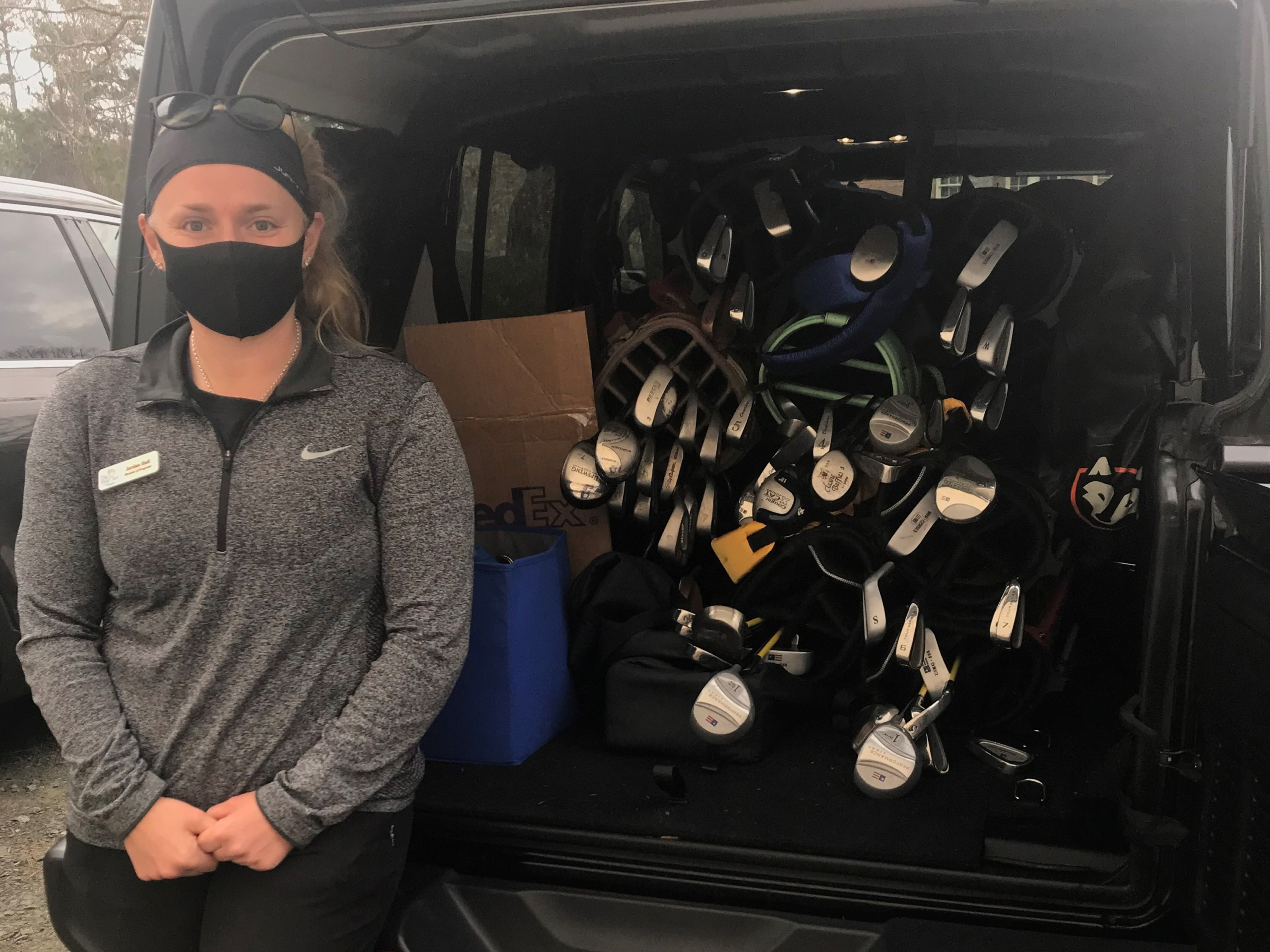 Woman wearing mask standing beside open trunk of SUV packed with golf clubs