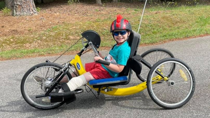 Boy sidts on yellow handcycle smiling at camera. He has a below the knee left leg amputation. He is wearing sunglasses and a helmet with mohawk spikes on it.
