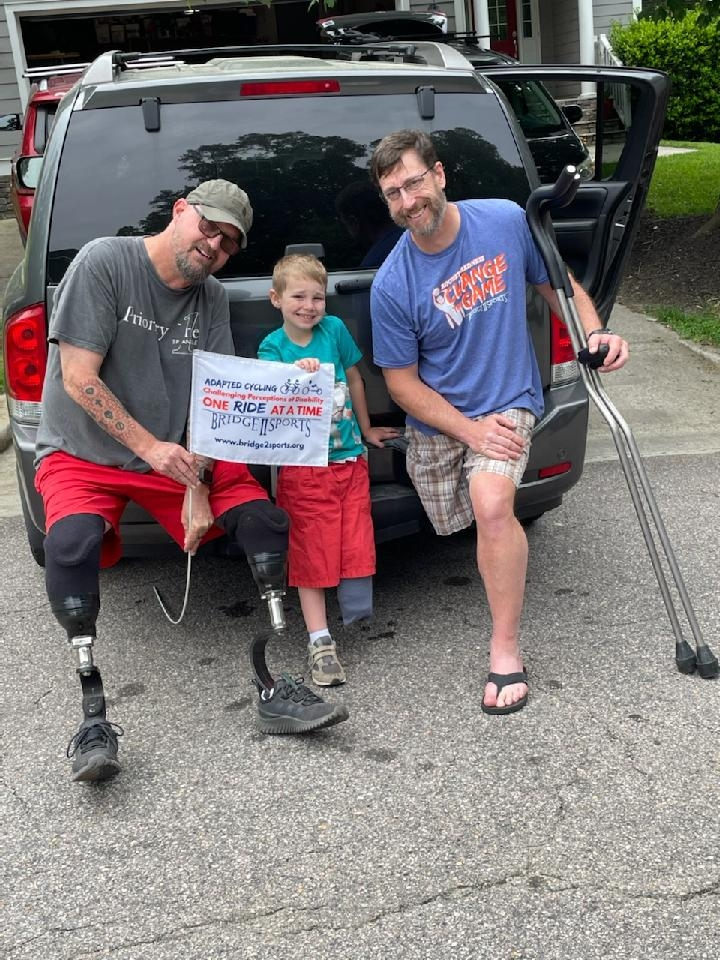 2 men are sitting on the bumper of a van posing with a young boy standing between them. The man on the left has 2 prosthetic legs and is holding a Bridge 2 Sports flag with the boy. The boy has a left leg amputation below the knee. The man on the right has a right leg amputation and is holding 2 crutches in his left hand. All are smiling widely.